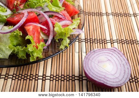 Closeup View On A Fragment Of A Translucent Plate With A Fresh Salad Of Raw Tomatoes