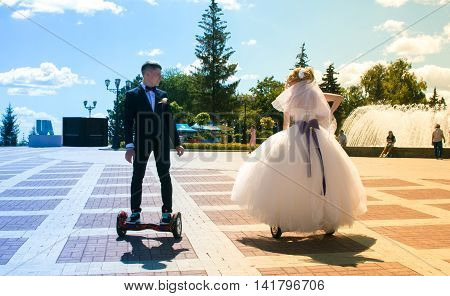 Bride and groom ride Segway against the background of a fountain