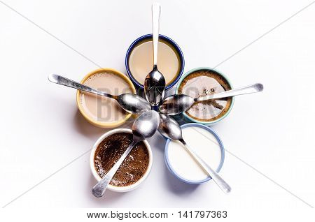 Cups with coffee, milk, juice, cappucino, Five cups placed in a circle with spoons. Healthy background. Colorful cups isolated on a white background.