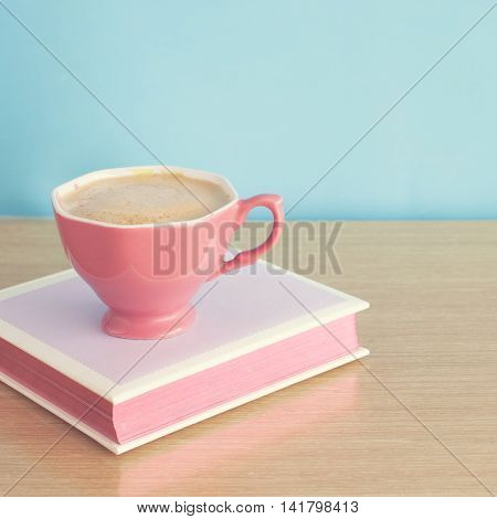 Pink cup of coffee over hardcover book
