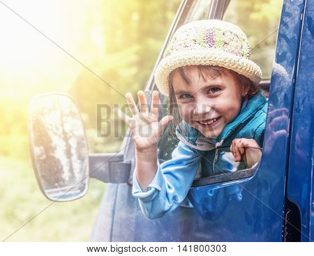 The little girl looks out the car window and waved his hand.