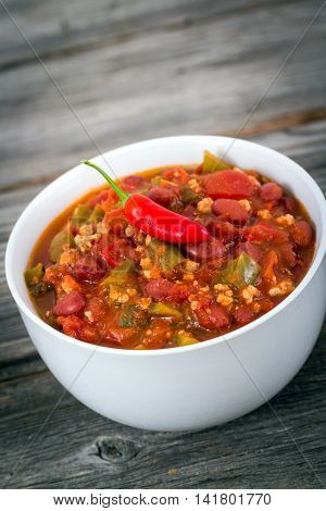 pork chili con carne bowl over a wood textured background