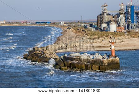 Pier with a lighthouse on the seashore next to the granary