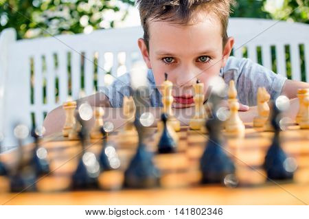boy thinking hard on chess combinations. boy playing chess outdoors. selective focus