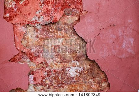 flaking plaster on the brick wall of an ancient building. old wall texture. peeling maroon paint, plaster and exposed brick wall.