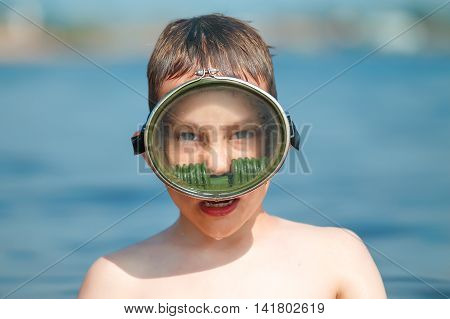 portrait of a boy in diving mask. child in the old mask swimming under water. boy just came to the surface and gasping. Closeup