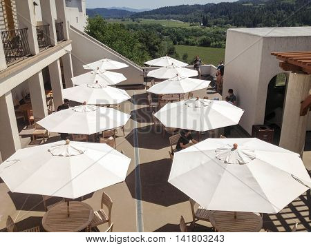 NAPA VALLEY, CALIFORNIA, APRIL 20, 2014: a view of  white sun umbrellas on the deck at Sterling Winery in the early afternoon, with lush green hills and meadow in the background