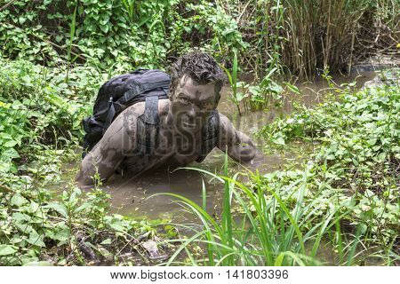 Adventurous man covered in mud wears backpack while hiking through deep muddy water and green vegetation in tropical wilderness