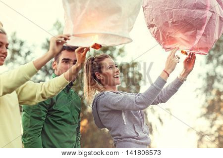 Picture showing group of friends floating chinese lanterns