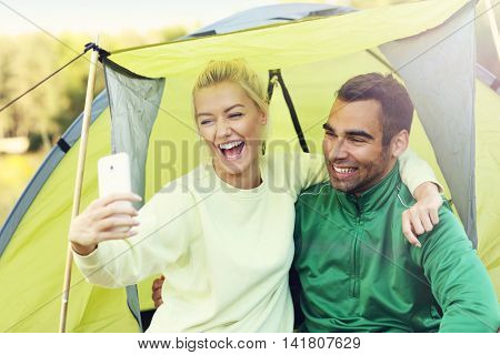 Picture showing couple camping in forest and taking selfie