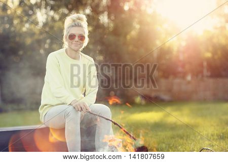 Young woman sitting close to campfire