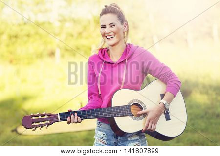 Picture of happy woman playing guitar outside