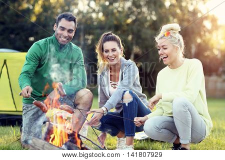 Picture showing group of friends preparing sausages on campfire