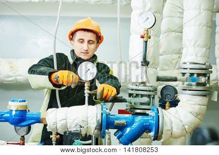 Technician or repairman installing manometer in boiler room