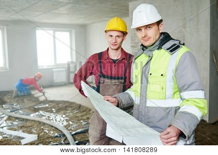 foreman builder and construction worker with blueprint in indoor apartment