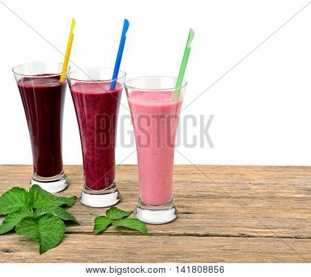 Smoothies made with fresh berries: blackberries, raspberries, red currants, black currants, strawberries on a wooden table. Isolated on white background.