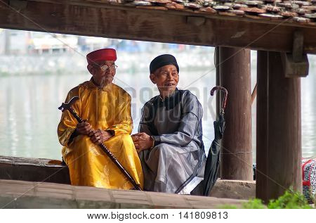 HA NOI, VIET NAM, July 8, 2016 the two old men, sit, where an ancient temple on the outskirts of Ha Noi, Vietnam