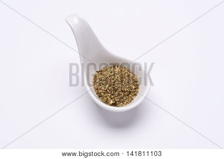 Monotone crushed Oregano leaves 1 tablespoon in a white spoon on the white background