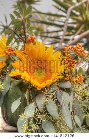 Holiday flower bouquet inside a gourd vase with red berries, green leaves and sprigs, and sunflowers on a rustic wood farm house background.