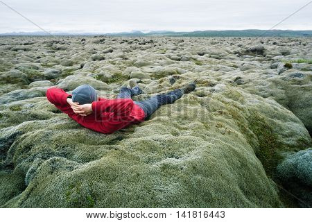 Man traveler in red jacket lying on the moss. Lava field on the south coast of Iceland, Europe. Tourist attraction. Amazing in nature. Cloudy summer day