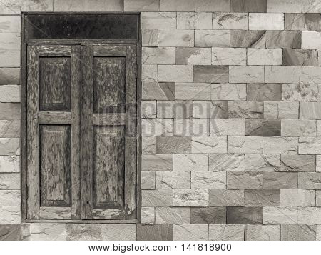 Old style wooden window and pattern glass on modern style square pattern limestone brick wall with copy space Sepia Selenium Tone