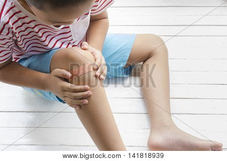 Children wound or The boy had an accident sitting on wooden white background.Top view and zoom in.