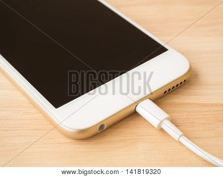 Close-up of gold smart phone charging with USB cable on wooden texture background