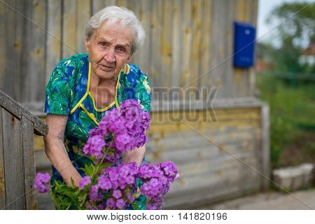 The old woman takes care of flowers near his rural home.