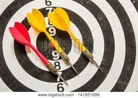 Three Red And Yellow Arrow In Bullseye Of Dartboard