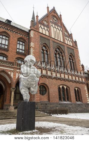 Riga, Latvia - January 1, 2016: The brick gothic building of Academy of Art in Riga with woman statue from mirror pieces.