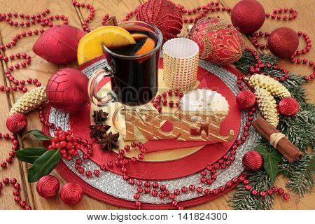 Christmas scene with noel sign, mulled wine, mince pie, gold and red bauble decorations, spices, holly and snow covered fir on oak background.