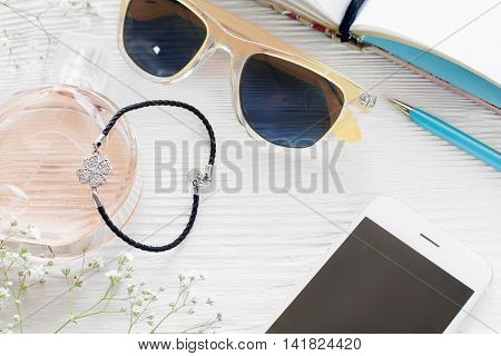 Fashionable woman workplace with female accessories. Smartphone with blank screen with sunglasses, perfume, bracelet, pen and notebook on white wooden table, mockup