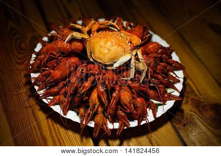 Large dish with boiled crawfish and crab on a wooden table. Beer Party. Beer plate. Beer Day. Oktoberfest. Beer tradition.
