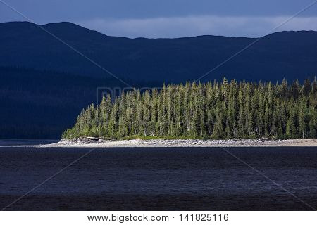 Forest, wood and lakeside in sunshine on a cape. Surrounded of dark water and mountains, ridges. Summer.