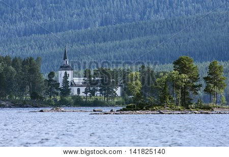 HOTAGEN, SWEDEN ON JULY 01. View of the Church in a distance across the lake Hotagen on July 01, 2016 in Hotagen, Sweden. Forests and ridge in the background. Built 1862. Editorial use.