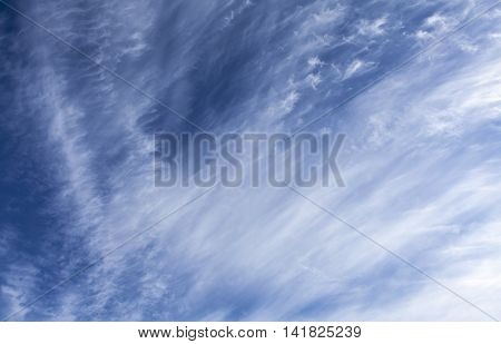 Some white clouds on a blue sky. Cirrus, high up on the sky.
