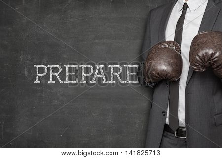 Prepare on blackboard with businessman wearing boxing gloves