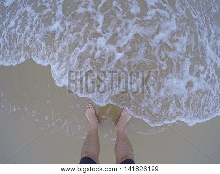 Fresh sea water touching male feet on sand.Above.Fish eye.