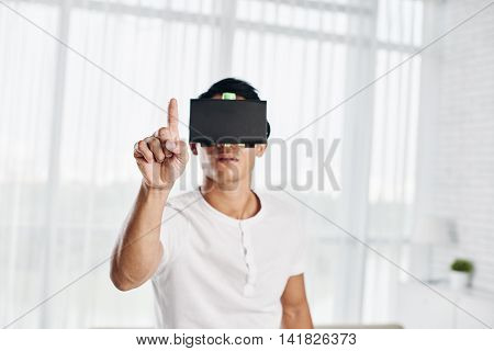 Asian man in VR glasses pushing invisible button