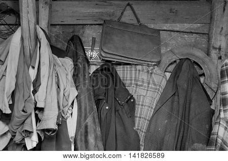 Front shot of shabby clothes and hand bag hanging on a rack in black and white