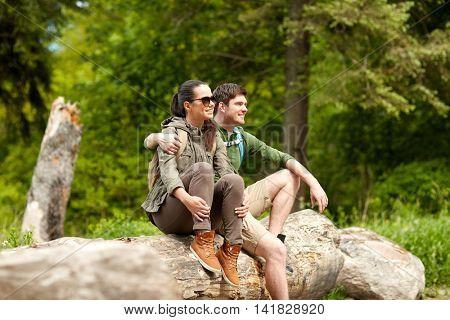 travel, hiking, backpacking, tourism and people concept - smiling couple with backpacks resting and hugging in nature