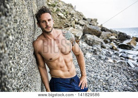 Handsome muscular shirtless man on the beach leaning on rock, looking at camera