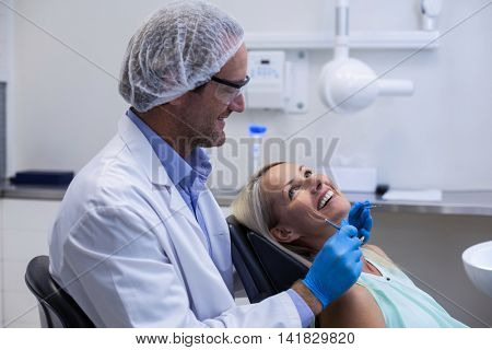 Male dentist interacting with female patient in dental clinic