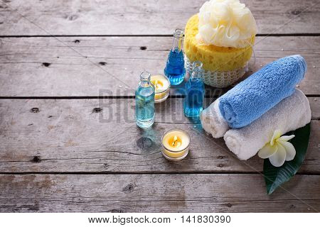 Spa or wellness setting in blue yellow and white colors. Bottles wih essential aroma oil towels candles and wispes on wooden background. Selective focus. Place for text.