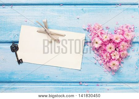 Background with heart from pink flowers and petals empty tag and vintage key on blue wooden planks. Selective focus. Place for text. Toned image.