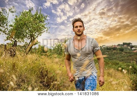 Good looking male model walking on grass in a field, looking at camera