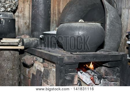 Looking retro fire burning stove with massive cast iron cooking pot on the top indoors closeup shot