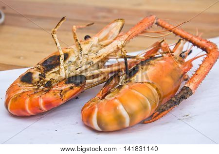 Two grilled prawns on wood table ready to eat