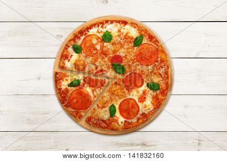 Delicious italian vegetarian pizza Margherita with tomato and cheese, thin pastry crust and one piece cut. Fast food top view at wooden desk on white wood table background