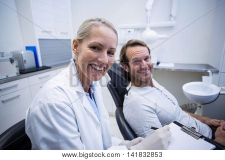 Female dentist writing on clipboard while interacting with male patient in dental clinic